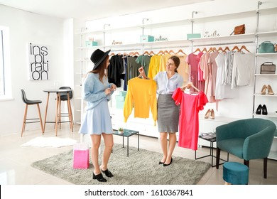 Seller helping young woman to choose clothes in shop