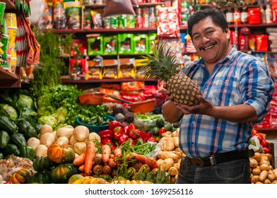 Seller holding an pineapple, in his grocery store.