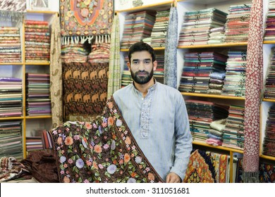 Seller from Kashmir in his colorful carpets store.Shallow doff