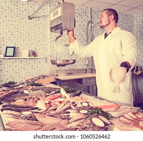Seller man in white cover-slut standing near fish counter and weight fish