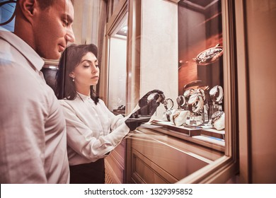 Seller shows the client an exclusive men's watch standing next to open showcase in the luxury jewelry store