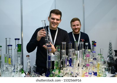 Seller standing at the counter and holding handmade glass bong for smoking marijuana, many bongs placed on a table. Cannabis fair (first in Ukraine held). October 11, 2019. Kiev, Ukraine