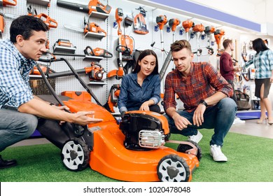 The seller in the store shows the customers a mowing machine. A young couple came to the garden tools store to buy equipment for gardening.