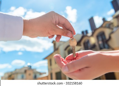 the seller transfers key to the house in the hands of the buyer outdoors