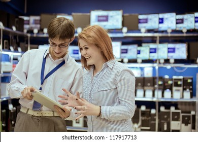 The seller-adviser shows the girl a new tablet computer