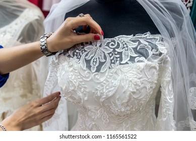 Seller's hands correcting bridal veil on mannequin in salon