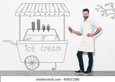 Selling the best ice cream. Handsome young smiling man in apron standing in front of the white wall and near the pencil drawn ice cream cart