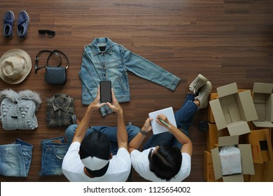 Selling online ideas concept small business owner, Top view Men and women  taking photo to shirts with cell telephone or smartphone digital camera on wooden floor with postal parcel box