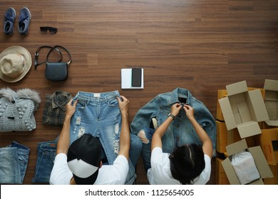 Selling online ideas concept small business owner, Top view men and women working shirts and jeans fashion from home on wooden floor with postal parcel box