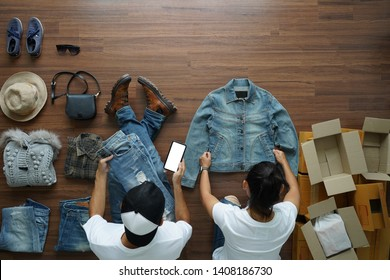 Selling online ideas concept small business owner, Top view men using smart phone and women working shirts and jeans fashion from home on wooden floor with postal parcel box