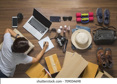 Selling online ideas concept, Top view of women working laptop computer on wooden floor from home with product and postal parcel