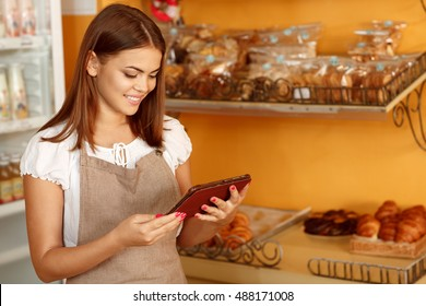Selling online too. Shot of an attractive woman working at her bakery using a digital tablet smiling joyfully copyspace on the side