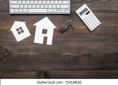 selling property online with paper house on office desk wooden background top view mockup