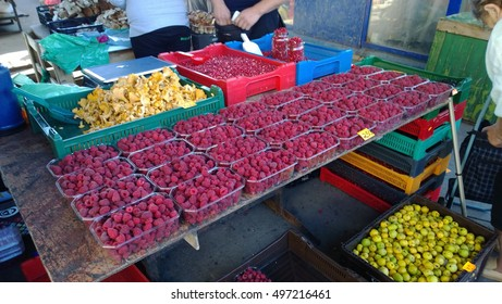 Selling raspberries, apples and mushrooms on the market