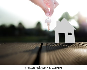 Selling real estate concept with house and key from real estate agent