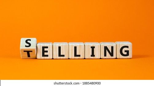 Selling or telling symbol. Turned wooden cubes and changed the word 'telling' to 'selling'. Beautiful orange background, copy space. Business and storytelling selling or telling concept.