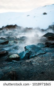 Seltun colorful geothermal stones area with steam and snow on the background in Iceland