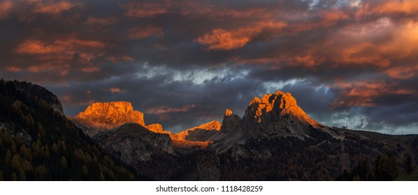Selva di Val Gardena, Scenic mountain landscape, Italian Dolomites with dramatic sunset and cloudy sky at background