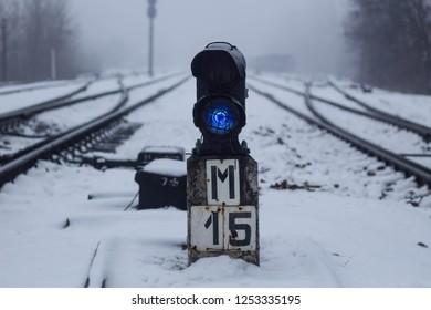 Semaphore on the railway in winter, glowing blue. Gloomy scene