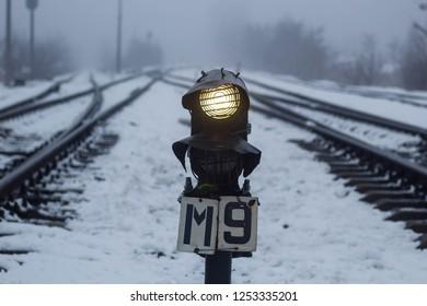 Semaphore on the railway in winter, glowing yellow. Gloomy scene