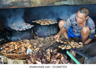 Semarang, Indonesia. June, 12 2018. Fisherman was smoke-dry a sea catfish to be preserved.