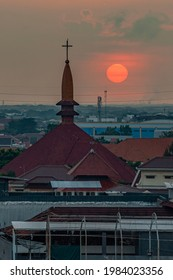 Semarang, Indonesia - May 26 2021 : Sunset view of Semarang with Catholic Church and Moslem Mosque as a foreground. Image contain Noise and Grain due to High ISO.