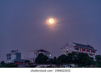 Semarang, Indonesia - May 27 2021 : Full circle moon above the Telkom building Semarang. Image contain Noise and Grain due to High ISO.