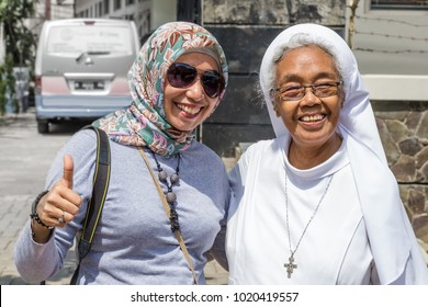 Semarang, Indonesia - November, 01, 2017:  A muslim woman and a catholic sister happy together in  Monastery Saint Franciscus in Semarang, central Java, Indonesia