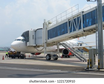 Semarang, Indonesia - October 28, 2018: A passenger boarding bridge connecting with an aircraft at Ahmad Yani International airport.