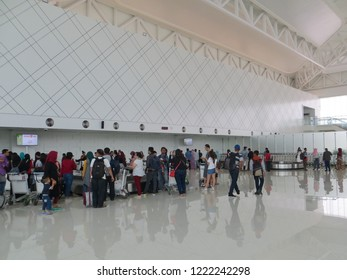 Semarang, Indonesia - October 28, 2018: The arrival passengers stand around the baggage conveyor waiting for their luggage to be unloaded from the plane in Ahmad Yani International airport.