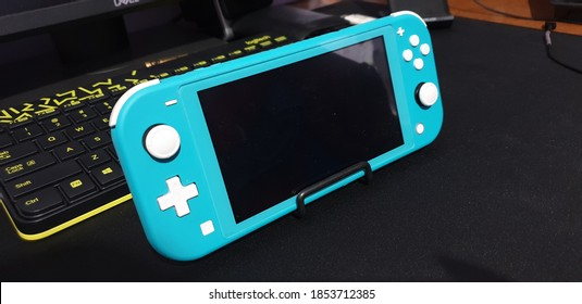 SEMARANG, INDONESIA - SEPTEMBER 20th, 2020 - Torquoise Nintendo Swith Lite Gadget Console on Black Matte Background