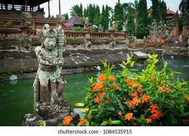 Semarapura, Bali / Indonesia - December 28 2017: View of a statue in the garden of Kertha Gosa temple with pond in the background