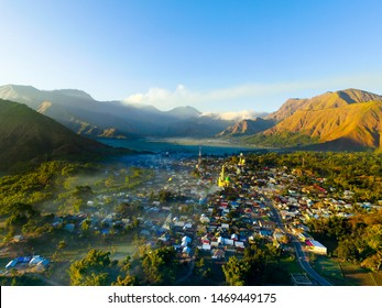Sembalun Village near Rinjani volcano in Lombok in the morning with sunrise and foggy view. Aerial Paddy Field