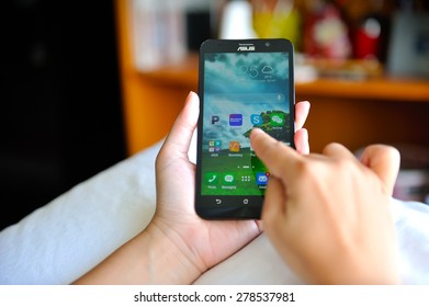 SEMBAWANG, SINGAPORE - MAY 17, 2015: Woman holding brand new Asus Zenfone 2. Social media are trending and both business as consumer are using it for information sharing and networking.