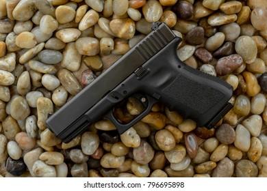 Semi auto handgun 9 mm. on stones background