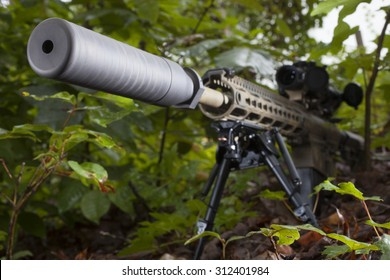 Semi automatic rifle with a suppressor in the trees