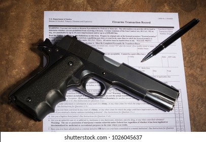 Semi automatic used handgun with pen and paperwork to complete the purchase