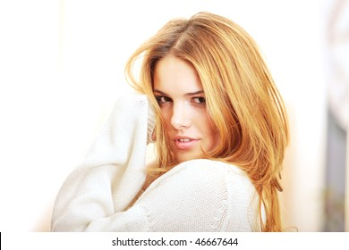 Semi Profile view of seductive blond gorgeous fashion model playing with her hair smiling to the camera in the morning in a light colored interior