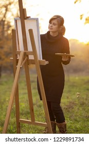 semi silhouette of beautiful young woman artist painting a picture on the easel, a figure with a brush and a palette of colors on the background of autumn landscape, a concept of hobby and creativity