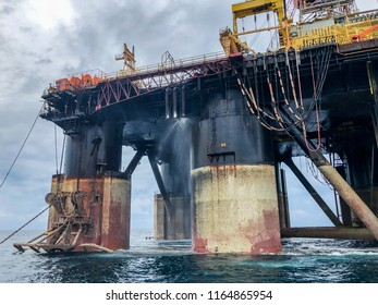 Semi submersible drilling rig view from crew vessel's deck. Rig deballasted so legs can be seen at all heights including the anchor rack