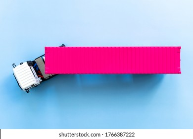 Semi trailer truck lorry cargo vehicle on blue background, View from above, Aerial top view of white semi truck with pink container cargo.