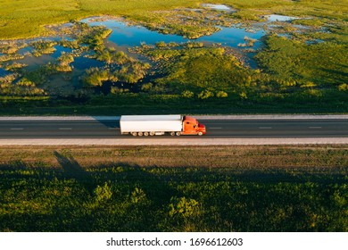 Semi truck with cargo trailer drive on road in green grass field with water at sunset, aerial drone view. Car with motion blur effect. Transportation background