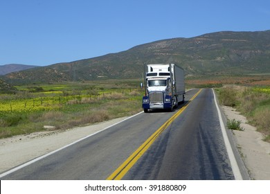 SEMI TRUCK DRIVING ON HIGHWAY, USA  - January 20, 2016: Semi truck going fast on the desert mountain highway