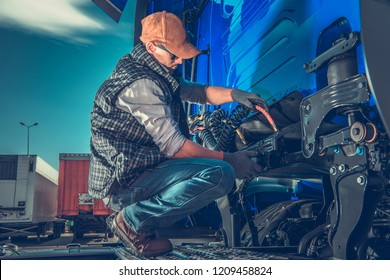 Semi Truck Maintenance. Caucasian Truck Mechanic Taking Care of Tractor Hydraulic and Electrical Trailer Outlets.