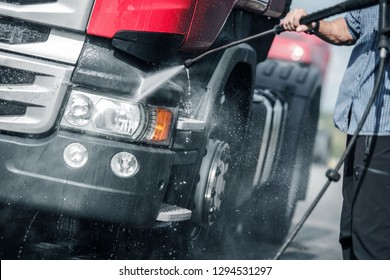 Semi Truck Pressure Washing by Caucasian Trucker. Automotive and Transport Industry.