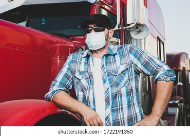 Semi truck professional driver on the job in casual clothing wears safety medical face mask. Confident looking trucker stands next to red big rig wearing protection sunglasses and surgical mask.