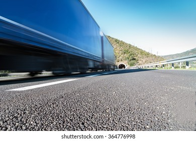 Semi truck speeding on the highway  - Transport industry concept with semitruck container driving to the tunnel on highway