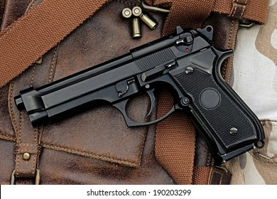 Semi-automatic handgun lying over a Leather handbag, 9mm pistol, Process HDR detail