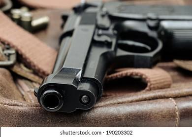 Semi-automatic handgun lying over a Leather handbag, 9mm pistol, Close-up Barrel.