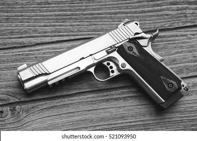 Semi-automatic handgun lying over wooden background, .45 pistol. (Black & White)